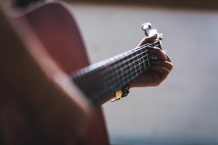 A woman fretting a chord on a guitar