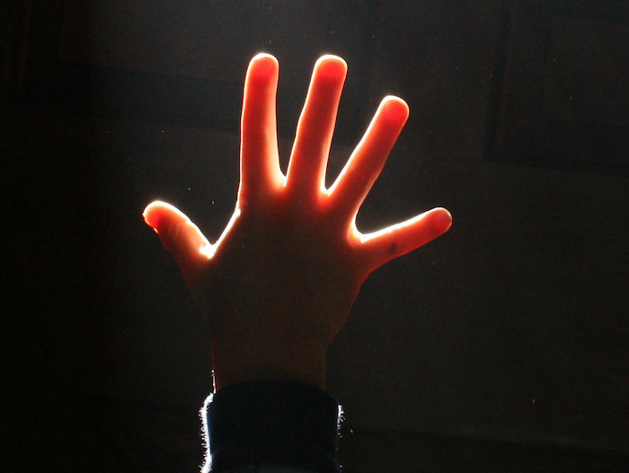 Five fingers being held up inside a dark music hall